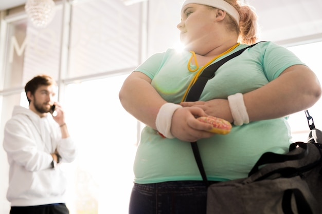 Mulher obesa escondendo comida de seu treinador