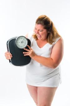 Mulher obesa, olhando com raiva em escala