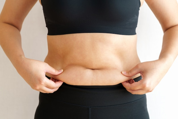 Mulher obesa segurando a gordura excessiva da barriga