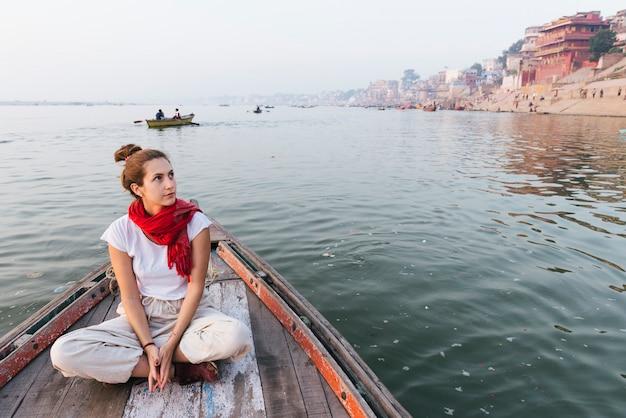 Mulher ocidental em um barco explorando o rio ganges