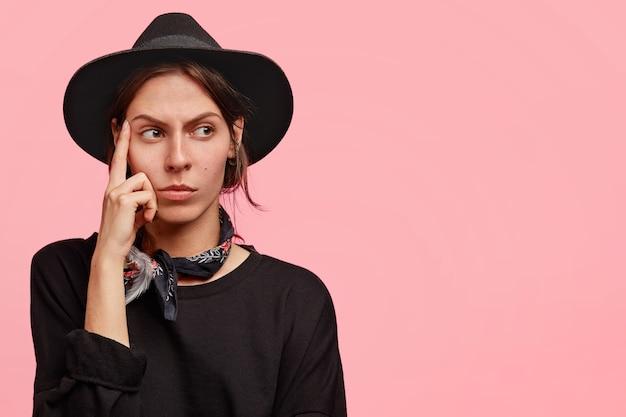 Mulher ocidental pensativa mantém o dedo da frente nas têmporas, contempla algo com expressão pensativa, tem olhar sério, usa roupas