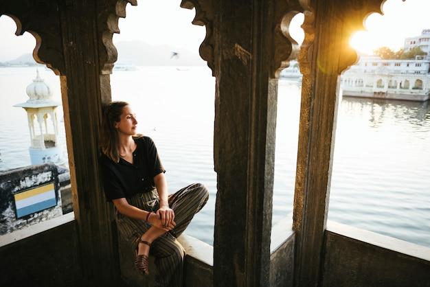 Mulher ocidental, sentando, ligado, um, cultural, arquitetura, em, udaipur, índia