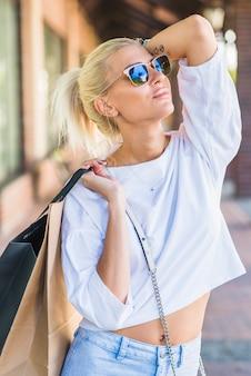 Mulher, óculos de sol, segurando, sacolas, ombro