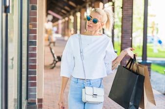 Mulher, óculos de sol, segurando, sacolas