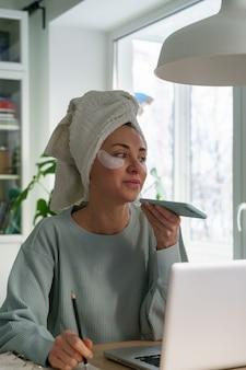 Mulher ocupada com toalha na cabeça e manchas sob os olhos, trabalhando em casa no laptop durante o bloqueio, grava uma mensagem de voz no telefone inteligente, faz anotações. beleza de cuidados com a pele do rosto. vida real.