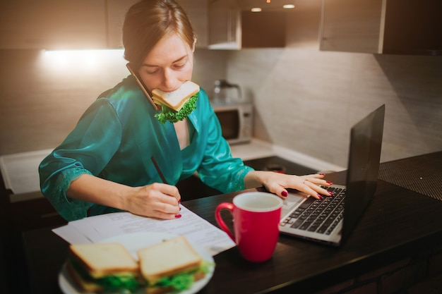 Mulher ocupada comendo, tomando café, falando ao telefone, trabalhando em um laptop ao mesmo tempo. empresária, fazendo várias tarefas. pessoa de negócios multitarefa. freelancer trabalha à noite.