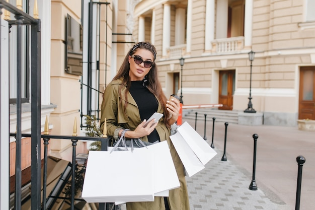Mulher ocupada de óculos escuros posando ao lado da loja com sacolas