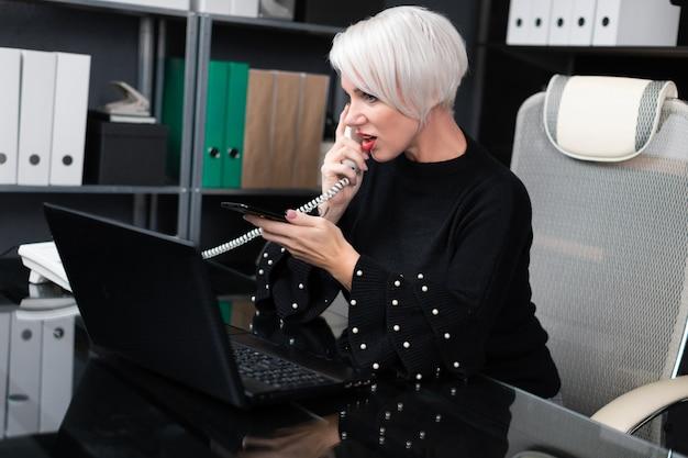 Mulher ocupada falando no celular e telefone fixo, sentado à mesa no escritório