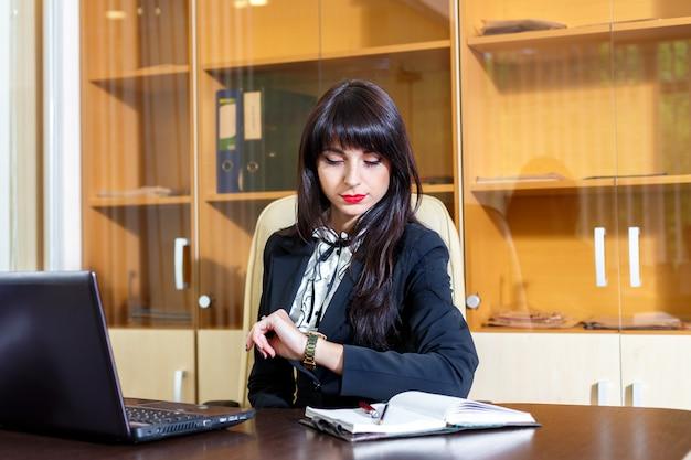 Mulher ocupada no escritório olhando para o relógio