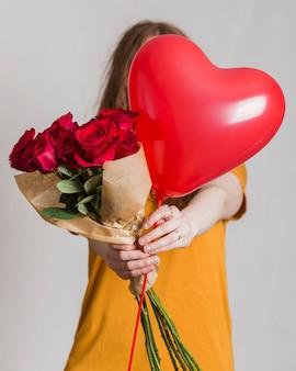 Mulher oferecendo um buquê de rosas e um balão