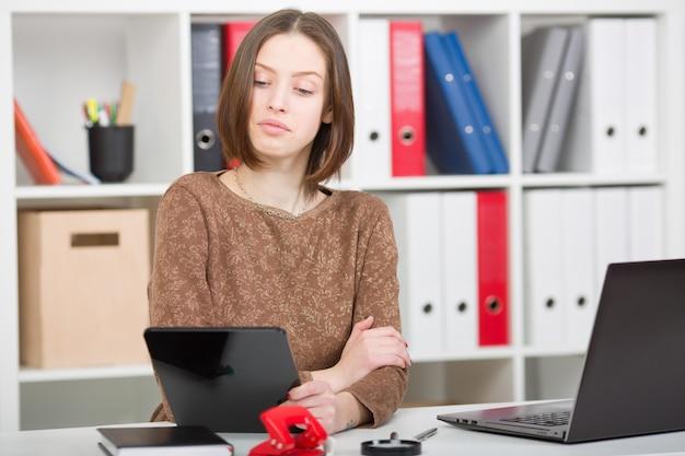 Mulher olha através de redes sociais no escritório. a avaliação olha para a tela do tablet.