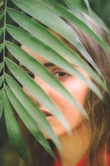 Mulher olha, câmera, através, folhas
