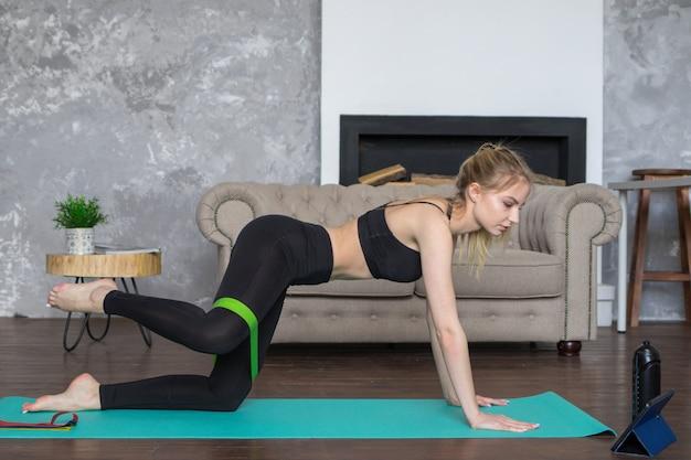 Mulher olha em um tablet e esportes, assentos de treino on-line em casa