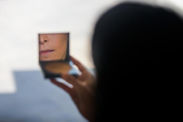 Mulher olha no pequeno espelho de seu pó