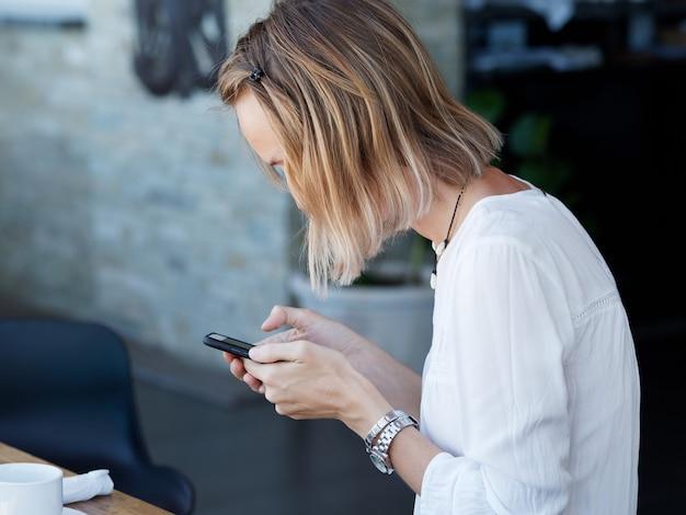 Mulher olha para a tela do smartphone no café durante o café da manhã. vista lateral. estilo de vida.