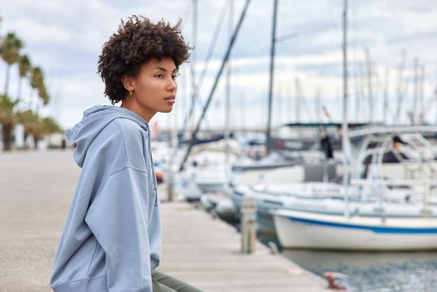 Mulher olha para barcos e iates no porto da marina fica perto da água na baía durante os fins de semana sonhos com a viagem usa moletom poses ao ar livre