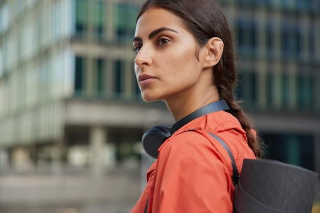 Mulher olha para longe e para longe usa fones de ouvido ao redor do pescoço faz passeios karemat pela cidade ao ar livre retorna para casa após exercícios leva estilo de vida ativo