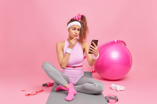 Mulher olha para tela de smartphone, figura esportiva verifica mensagens ou feed de notícias em redes sociais fica em um tapete confortável