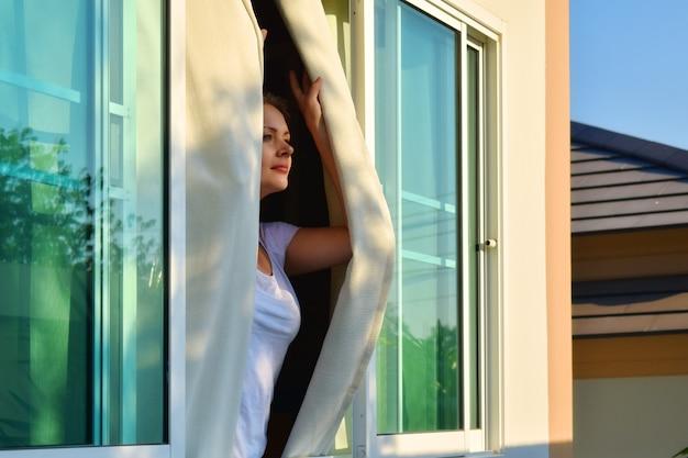 Mulher olha pela janela em um dia ensolarado.