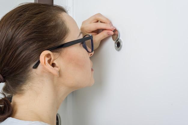 Mulher olha pelo olho mágico da porta da frente no apartamento