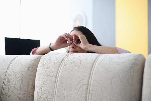 Mulher olha por trás do sofá e segura as mãos como binóculos