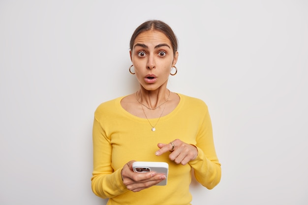 Mulher olha surpresa indica que a tela do smartphone moderno não consegue acreditar em notícias surpreendentes e chocantes usa um suéter amarelo sobre branco