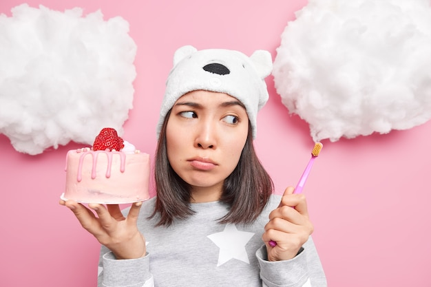 Mulher olha tristemente para a escova de dentes tem problemas com os dentes porque come muito doce contém um bolo delicioso