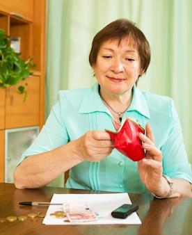 Mulher olhando a contagem de dinheiro preocupada