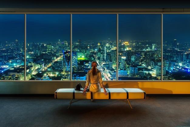 Mulher olhando a paisagem urbana à noite