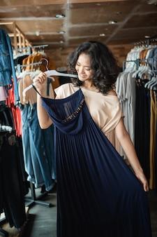 Mulher olhando algumas roupas na loja de moda