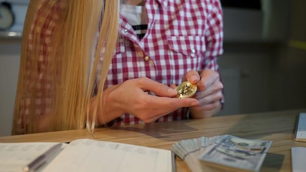 Mulher olhando atentamente bitcoin nas mãos