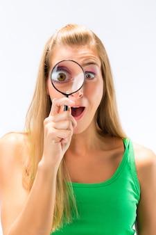 Mulher olhando através de lupa ou lupa