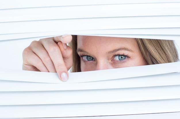 Mulher olhando através de persiana