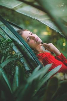 Mulher, olhando câmera, através, plantas