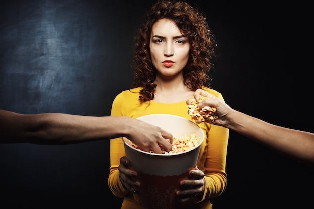 Mulher olhando direto segurando balde de pipoca enquanto amigos pegam comida