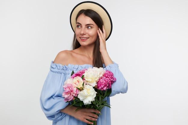 Mulher olhando feliz com cabelo comprido morena. usando um chapéu e um lindo vestido azul. segurando um buquê de flores, tocando o cabelo