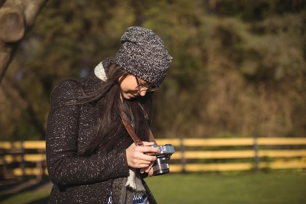 Mulher olhando fotos na câmera digital