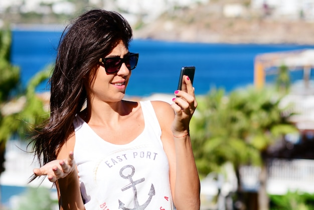 Mulher olhando incrédulo o seu celular