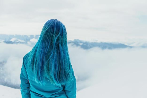 Mulher olhando montanhas no inverno