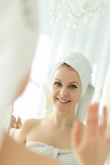 Mulher olhando no espelho com uma toalha na cabeça depois do banho