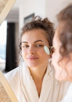 Mulher olhando no espelho e fazendo massagem facial