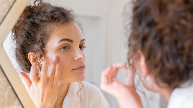 Mulher olhando no espelho e fazendo uma rotina de beleza facial
