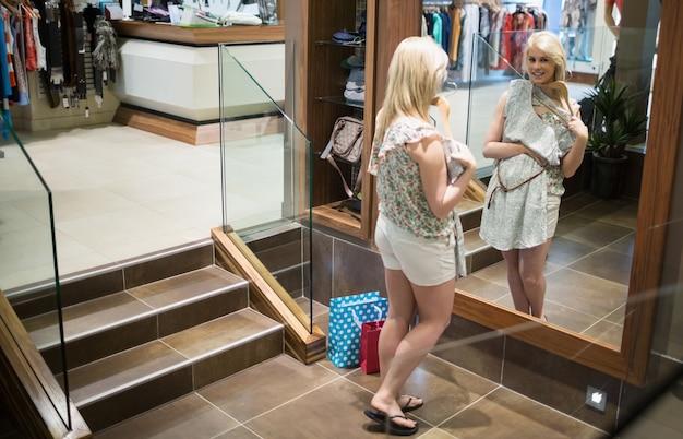 Mulher olhando no espelho segurando roupas