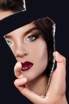 Mulher olhando no pedaço de espelho