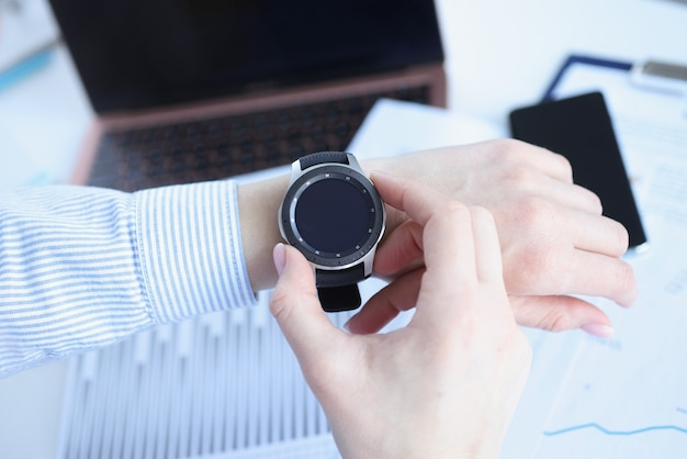 Mulher olhando o relógio inteligente no local de trabalho closeup. conceito de prazo