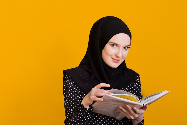Mulher olhando para a câmera segurando o livro na mão sobre a superfície