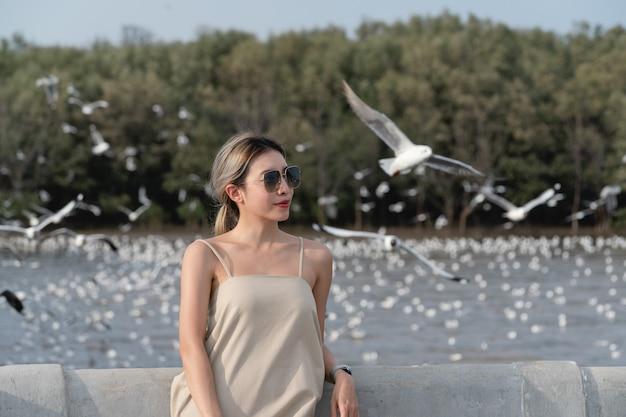 Mulher olhando para a costa com gaivotas voando no fundo, sentindo-se livre