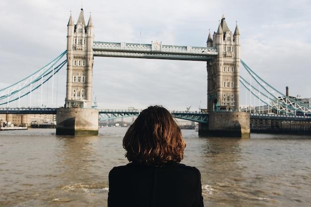 Mulher olhando para a famosa tower bridge st uk durante o dia tower bridge no reino unido