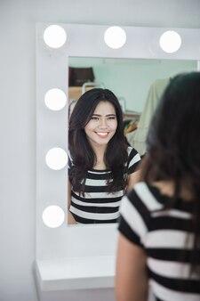 Mulher olhando para a pele no espelho