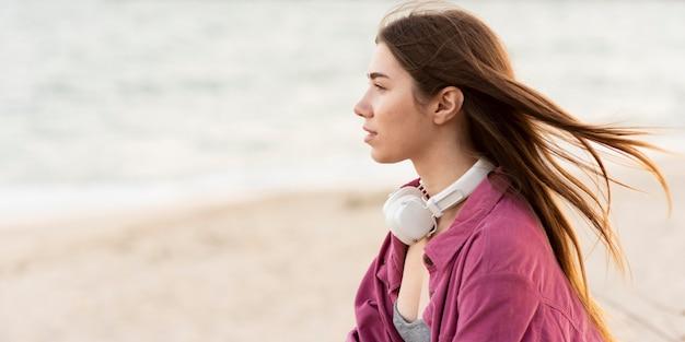 Mulher olhando para a praia de lado